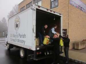 Wilmer and Junior help load food donated by parishioners of St. Mary's Church in Pompton Lakes, N.J., onto a truck for delivery to people in need.