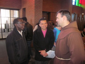 Fr. Jacek Orzechowski, OFM, guardian of St. Camillus Friary in Silver Spring, Md., greets postulants Junior Joseph and Wilmer Garcia.