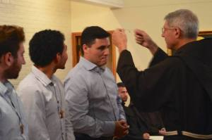 Postulant director Fr. Ron Pecci, OFM, gives Tau cross to Javier del Angel de los Santos as other postulants look on during Aug. 26 reception ceremony.